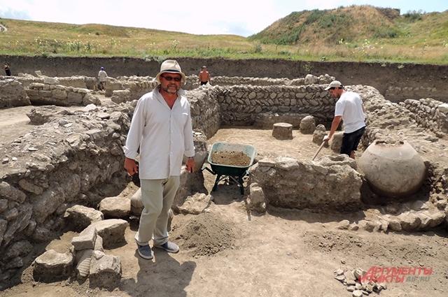 Владимир Кузнецов на фоне остатков одного из строений на раскопе «Нижний город», где нашли много хорошо сохранившихся пифосов и амфор.