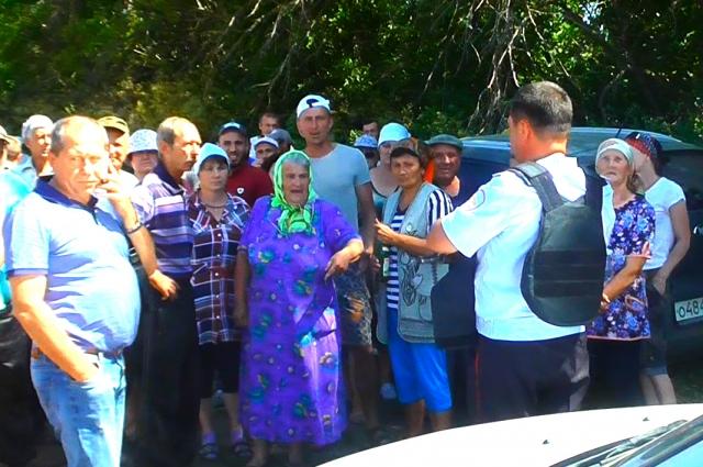 Приехавшего к жителям агронома охраняет полицейский с автоматом.
