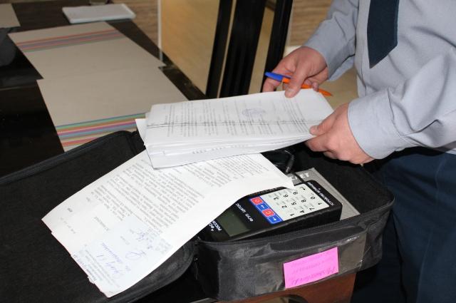 Перед тем, как закрепить браслет на ноге арестованного или заключённого, инспектор заполняет и подписывает необходимые документы.