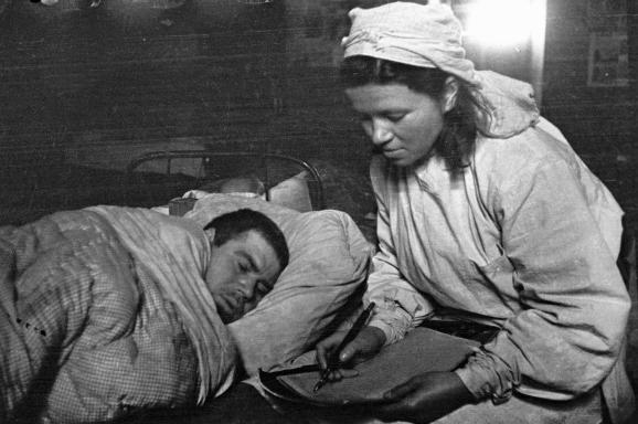 Сестра медсанбата пишет письмо родным под диктовку раненого солдата. 1-ый Прибалтийский фронт
