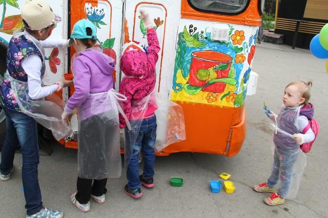 Дети разных возрастов рисуют на троллейбусе.