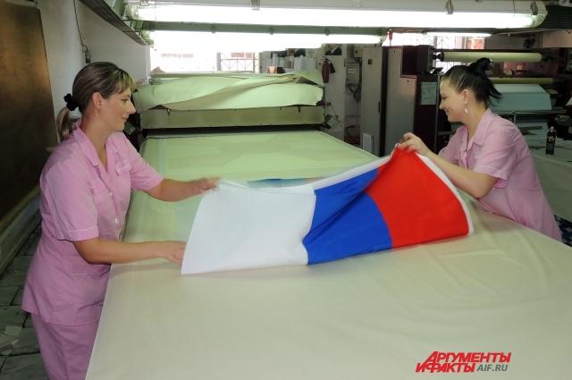 Работницы сублимационного цеха складывают еще горячий российский триколор, который скоро будет висеть в чьем-то кабинете.