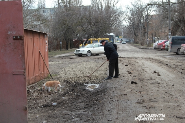 Василий Кривулька заделывает дырки на дороге, образованные от тяжелой коммунальной техники.