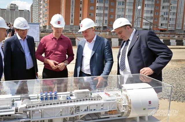 Мэр Москвы Сергей Собянин (в центре) и глава стройкомплекса Марат Хуснуллин (второй справа) рассматривают модель тоннелепроходческого щита на строящейся станции «Некрасовка».