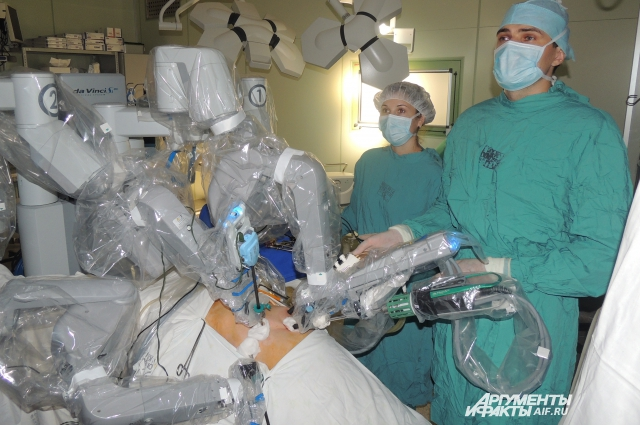 Над пациентом находятся врач-ассистент и операционная медсестра, которые постоянно следят за ходом операции