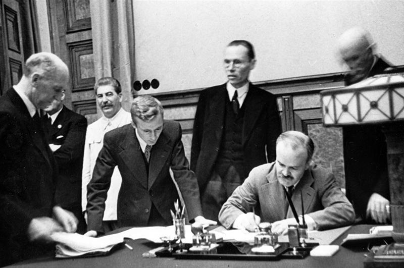 Подписание договора о дружбе и границе между СССР и Германией. В. Молотов подписывает договор. Стоят (слева направо) Иофхим фон Риббентроп, И. Сталин, В. Павло, Ф. Гаус