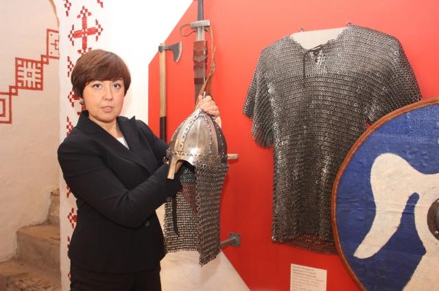 Галина Широкова показывает шлем их экспозиции музея.