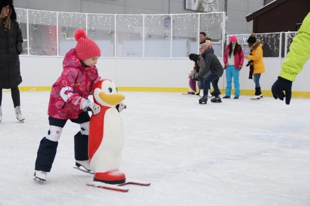 Дети учатся кататься на коньках вместе с тренировочными пингвинами.